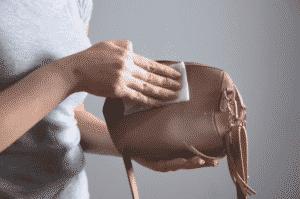 Donna che pulisce borsa in pelle con panno morbido